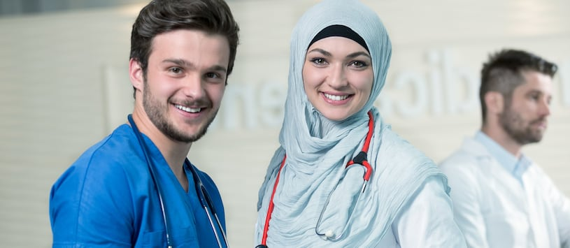A man wearig blue scrubs with a hijab-wearing female doctor. Take Healthcare Diploma Programs at Oxford.