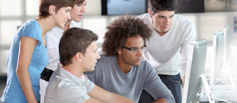 A man stares at a computer intently surrounded by a group of people watching. Take Information Technology Diploma Programs at Oxford.