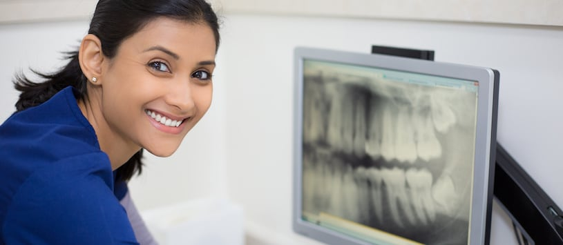 A woman smiling in from of a dental x-ray. Take the Intra Oral Dental Assisting Program at Oxford College.