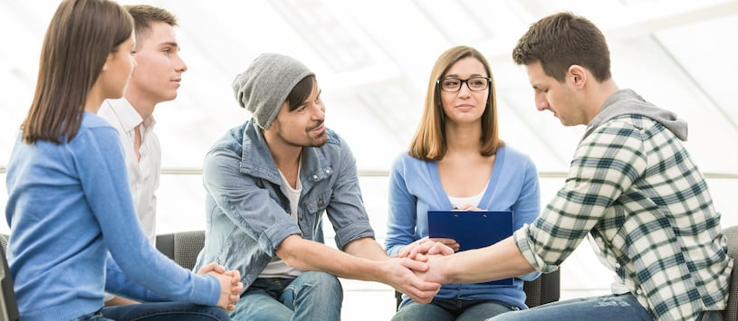 A counsellor comforting someone in a group therapy session. Take Community Service Diploma Programs at Oxford.