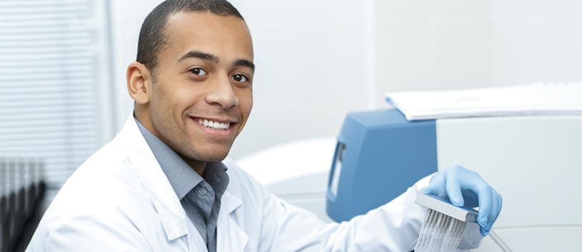 A clinical researcher in the lab smiling. Take the Clinical Research Program at Oxford.