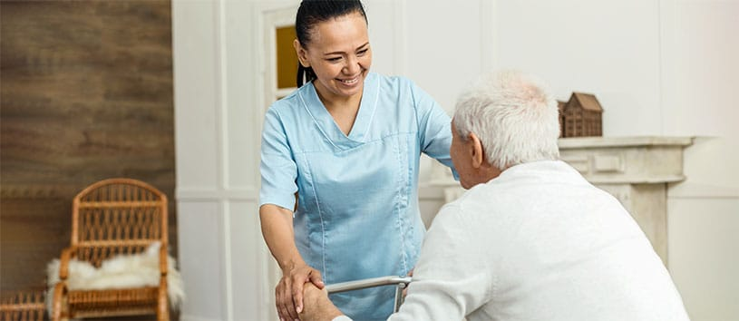 A PSW helping an elderly gentleman. Take the Personal Support Worker Program at Oxford.