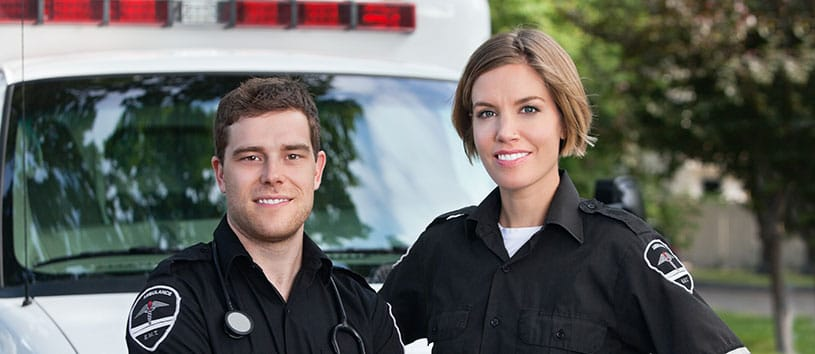 Two paramedic students stand outdoors in front of an ambulance