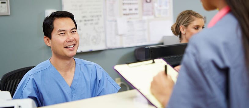 A medical office assistant at a desk. Take the Medical Office Assistant Program at Oxford!