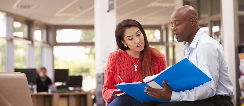 A Financial Aid advisor sits with a student and shows her a binder.