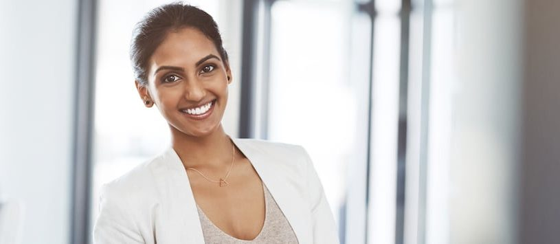 A beautiful business woman smiling with neutral tones. Take a Business Management Program at Oxford.