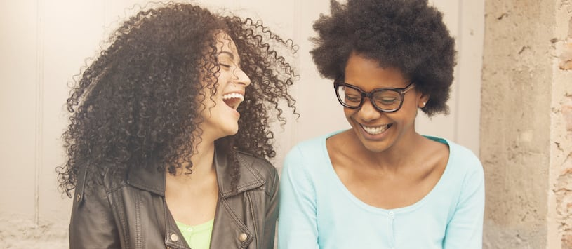 Two women of colour who are in their early twenties and hip laughing together