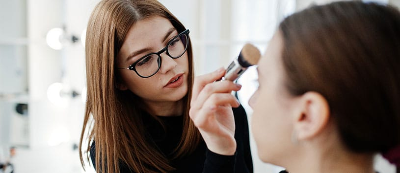 A woman applying makeup. Take your Advanced Esthetics and Spa Operations Program at Oxford.