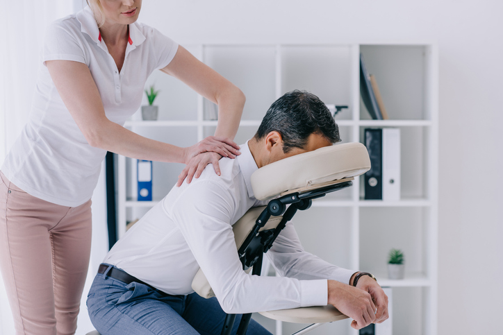 Man receiving seated massage from a masseuse.