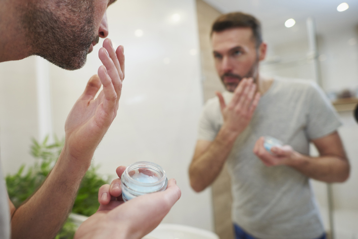 Man applying beauty product in the bathroom