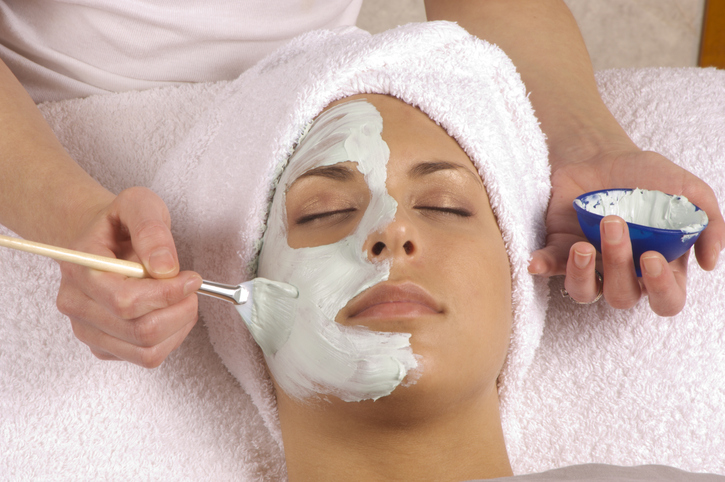 Woman having a face mask applied to her face.