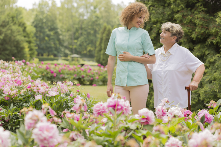 Shot of a happy elderly woman walking with her nurse around the garden
