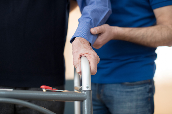 Senior Man's Hands On Walking Frame With Care Worker In Background