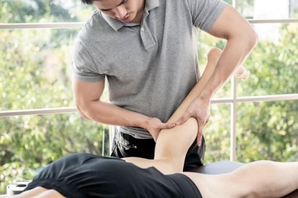 Male masseuse massaging a client's leg.