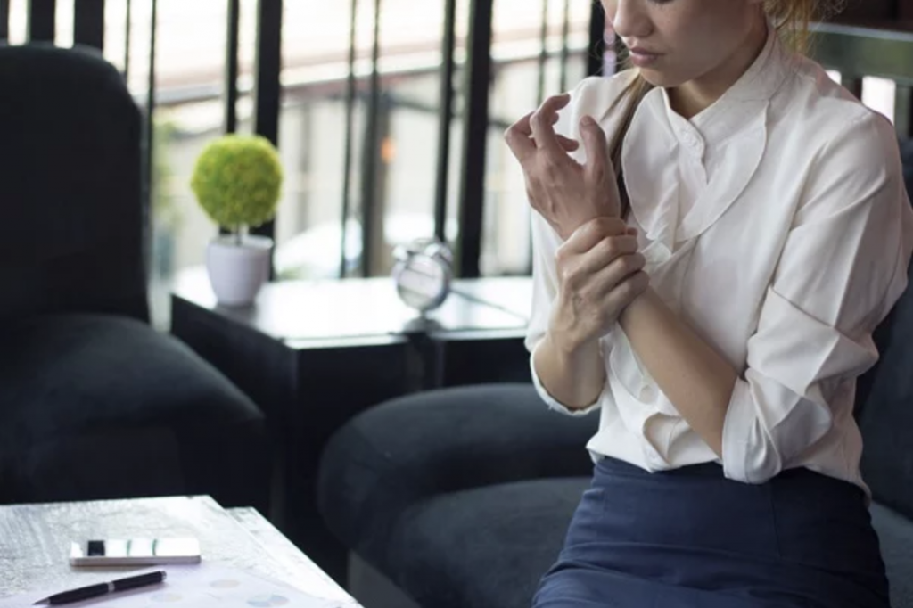 Woman rubbing her wrist which appears to be in pain.