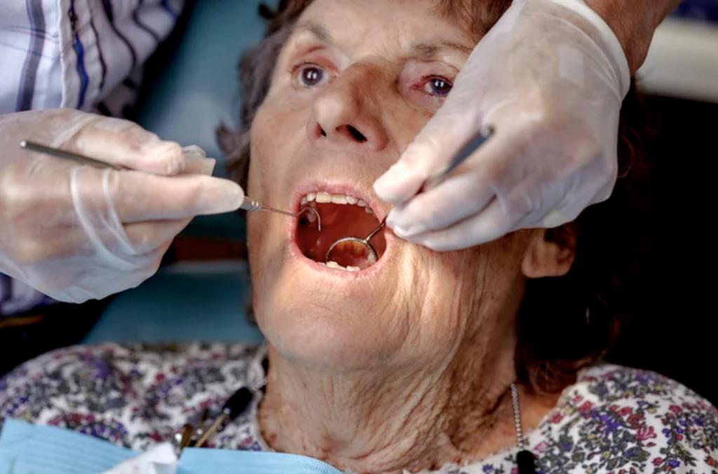 Senior woman having her teeth examined by a Dental Hygienist.